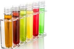 Reageerbuizen met multikleurenchemische producten in wit stock fotografie