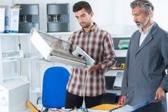 2 reairmen checking radiator before repairing it stock photo