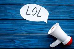 Reakcja coś śmieszny Internetowy meme LOL Megafon blisko chmurnieje z słowem LOL na błękitnego drewnianego tła odgórnym widoku zdjęcie stock
