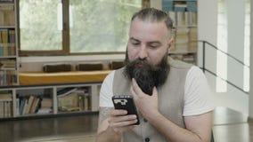Reakcja młody człowiek zatwierdza jego kierowniczego tak i skinie z brody czytaniem coś na jego mądrze telefonie - zdjęcie wideo