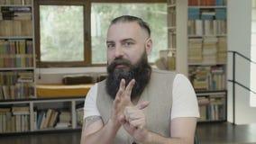 Reaktion eines jungen Geschäftsmannes mit dem Bart, der allein im Büro erschreckend und von den Geräuschen erschrocken herum scha stock footage