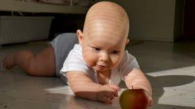 Reaktion ett gammalt halvår behandla som ett barn pojken med äpplet som ligger på golvet stock video