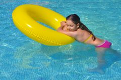 Real adorable girl relaxing in swimming pool stock photo