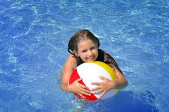 Real adorable girl relaxing in swimming pool Stock Photos