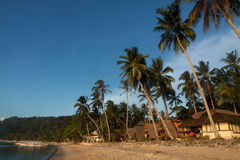 Real beach life on island of Palawan, Philippines. Sandy beach with bungalows and a boat near the island of Busuanga. Philippines Stock Photos