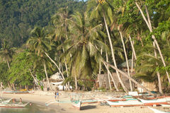 Real beach life on island of Palawan, Philippines. Sandy beach with bungalows and a boat near the island of Busuanga. Philippines Royalty Free Stock Image