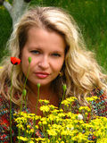 The real beauty. A young charming woman in  a green garden with yellow and red flowers- an ideal of woman and beauty Royalty Free Stock Photo
