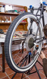 Real bicycle mechanic repairing custom fixie bike. Real bicycle mechanic repairing black custom fixie bike in the workshop royalty free stock photos