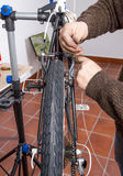 Real bicycle mechanic repairing custom fixie bike. Real bicycle mechanic repairing black custom fixie bike in the workshop stock photography