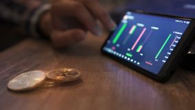 Real bitcoin coins on table. Block-chain, trading online, Cryptocurrency trend graph. Man touching screen, chart. Forex