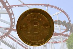 Real bitcoin with roller coaster in background stock images
