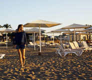 Real blrunette girl along on seacost walking, healthy at sunrise, hotel resort Stock Image
