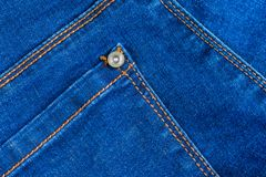 Real blue jeans denim fabric background texture. empty back pocket with yellow orange stitching and rivet royalty free stock photos