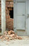 Real burglary. Broken hole in the brick wall near the door (real Royalty Free Stock Image