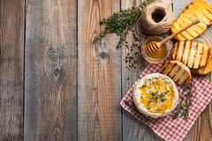 A real Camembert from France with thyme, honey and toasted bread on old wooden rustic table. Soft cheese on a wooden background wi. Th copy space. Top view Stock Photography
