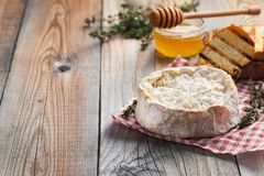 A real Camembert from France with thyme, honey and toasted bread on old wooden rustic table. Soft cheese on a wooden background wi. Th copy space Royalty Free Stock Photography