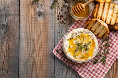 A real Camembert from France with thyme, honey and toasted bread on old wooden rustic table. Soft cheese on a wooden background wi. Th copy space. Top view Stock Photo
