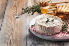 A real Camembert from France with thyme, honey and toasted bread on old wooden rustic table. Soft cheese on a wooden background wi. Th copy space Stock Photo