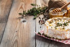 A real Camembert from France with thyme, honey and toasted bread on old wooden rustic table. Soft cheese on a wooden background wi. Th copy space Royalty Free Stock Image
