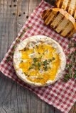 A real Camembert from France with thyme, honey and toasted bread on old wooden rustic table. Soft cheese on a wooden background. T. Op view Royalty Free Stock Photos