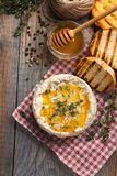 A real Camembert from France with thyme, honey and toasted bread on old wooden rustic table. Soft cheese on a wooden background. T. Op view Stock Images