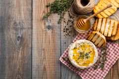 A real Camembert from France with thyme, honey and toasted bread on old wooden rustic table. Soft cheese on a wooden background wi. Th copy space. Top view Royalty Free Stock Photo