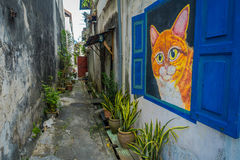 Real cat and a colorful street art graffiti cat in George Town city centre. Real cat and a colorful street art graffiti cat in George Town city centre, Malaysia Stock Photography