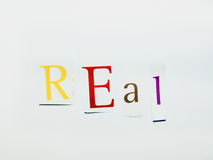 Real - Cutout Words Collage Of Mixed Magazine Letters with White Background. Caption composed with letters torn from magazines with White Background Royalty Free Stock Image