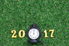 2017 real 3d objects on green grass with luxury pocket watch, happy new year concept Royalty Free Stock Photo