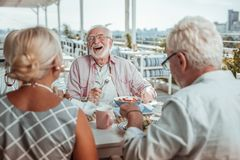 Positive delighted mature man laughing at joke. Real emotions. Group of elderly people being on terrace while having dinner together royalty free stock image