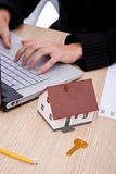 Real estate. Concept with a house; businesswoman and laptop Royalty Free Stock Photography