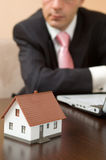 Real estate. Concept with a house and businessman at the office Stock Images