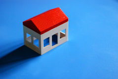 Real Estate. A small toy house on a blue background, representing new real estate Stock Images