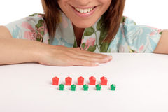 Real estate. Pretty young woman playing with toy houses, real estate Stock Photography