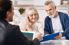 Real estate advisor working with aged couple in the house. Discussing all details. Attentive cheerful concentrated old couple sitting at home and concluding Stock Photo