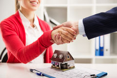 Real estate agency. Two business people shaking hands as successful agreement in real estate agency office. Concept of housing purchase and insurance Stock Images