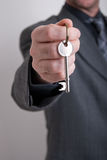 Real estate agent. A real estate agent holds out the front door key of a new home to a lucky buyer Stock Photos