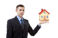 Real estate agent. Young real estate agent holding a small house royalty free stock photography