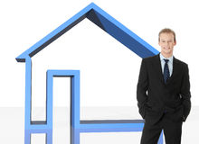 Real estate agent. Young businessman standing in front of big blue 3d home. Real estate or insurance concept Stock Photo