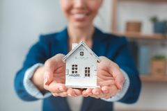 Real estate agent at agency sitting holding house model close-up joyful blurred background stock photos