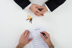 Real Estate Agent With Customer Signing Contract At Desk. Directly above shot of real estate agent with customer signing contract at desk Royalty Free Stock Photo