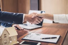 Real estate agent and customers shaking hands together celebrating finished contract after about home insurance and investment lo royalty free stock photography