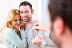Real estate agent delivers keys of new house to young couple Royalty Free Stock Photography