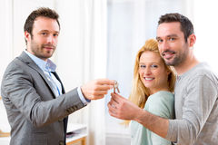 Real estate agent delivers keys of new house to young couple Stock Photography