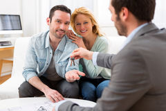 Real estate agent delivers keys of new house to young couple Royalty Free Stock Images