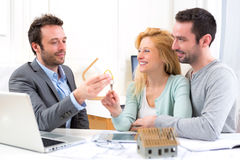 Real estate agent delivers keys of new house to young couple Royalty Free Stock Image
