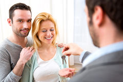 Real estate agent delivers keys of new house to young couple Stock Photo