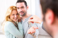 Real estate agent delivers keys of new house to young couple Royalty Free Stock Photo