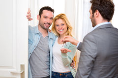 Real estate agent delivers keys of new house to young couple Stock Images
