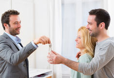 Real estate agent delivers keys of new house to young couple Stock Image